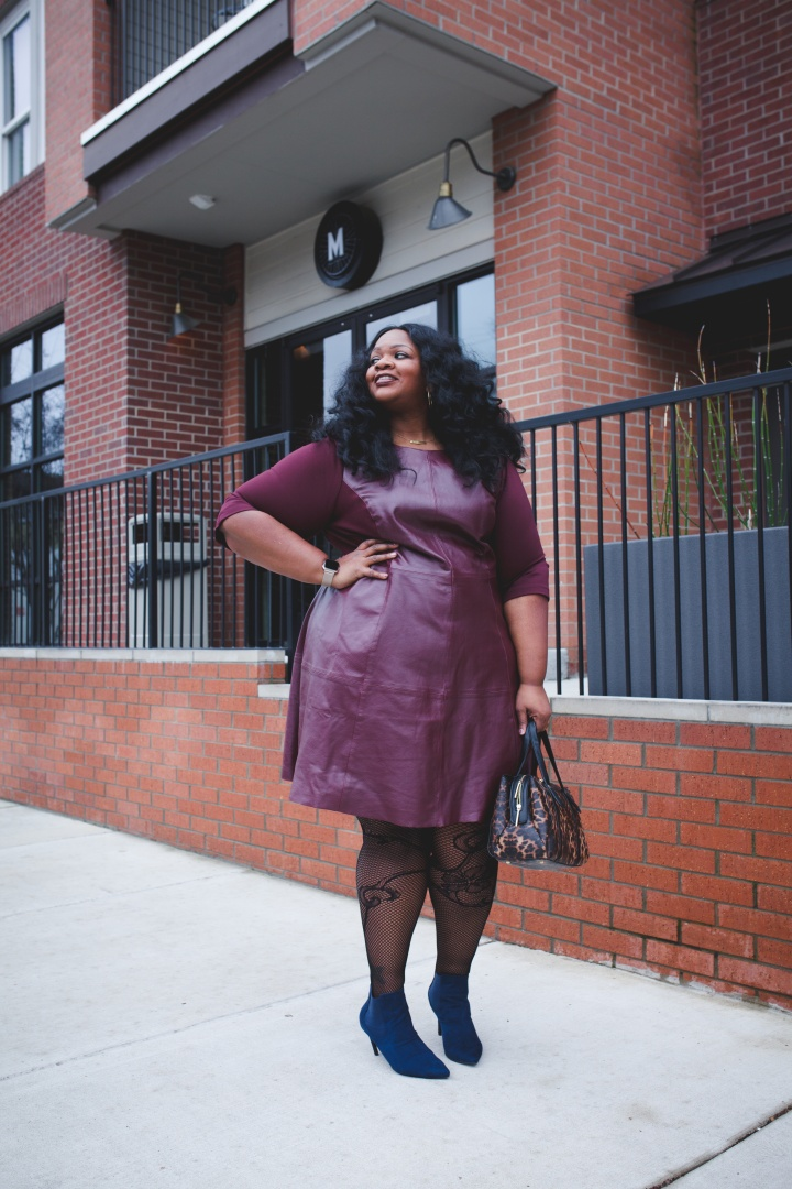 Plussize Blogger wearing leather dress. Color is maroon. Woman has curly hair.